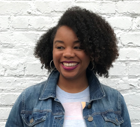 Khalilah Johnson in a denim jacket in front of a white brick wall