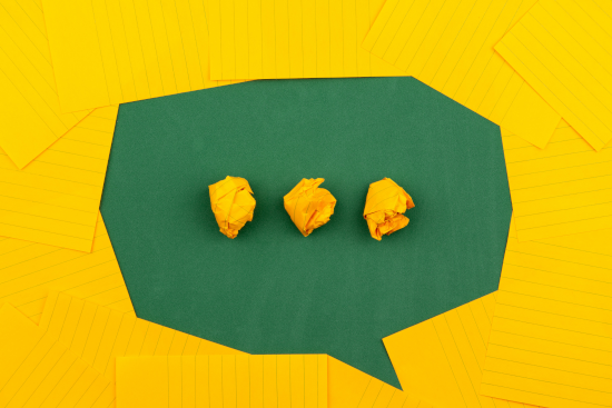 yellow paper surrounding green paper with three crumpled pieces of yellow paper, all shaped to indicate talking