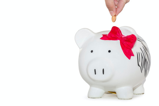 picture of a hand putting a coin in a piggy bank that has a little bow on its head